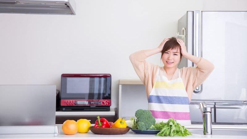 キッチンで頭を抱える女性